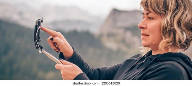 Hiking woman taking panoramic picture of summer mountain landscape. Selfie photo stick. Zabljak Durmitor, Montenegro