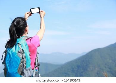 hiking woman taking photo with phone at mountain peak