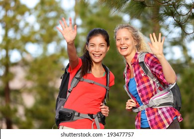 Hiking women waving hello with hands smiling at camera happy during hike trek outdoors in forest. Two beautiful girls living active healthy lifestyle doing outdoor activities trekking wearing backpack