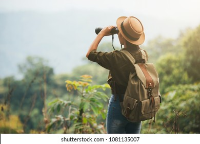 Hiking young woman with binoculars, Hiking concept.
