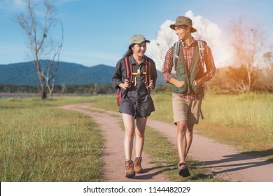 Hikings couple asian walking travel together at forest for camping on holiday weekend talking about something on the go near river and mountain view.