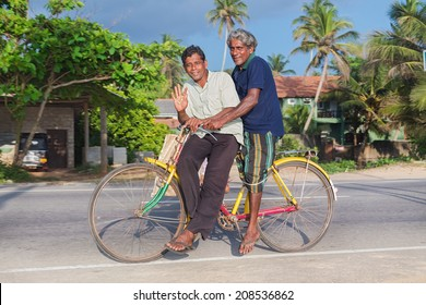 HIKKADUWA, SRI LANKA - FEBRUARY 24, 2014: Two local men on colourful bicycle. Cycling is the main transportation for the traditional people in the country.