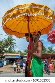 HIKKADUWA, SRI LANKA, SEPTEMBER 08, 2013 : A Temple Priest is sheltered under a yellow umbrella by an attendant whilst parading down the coastal road during the Buddhist perahera (procession).