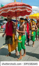 HIKKADUWA, SRI LANKA, SEPTEMBER 08, 2013 : A Temple Priest is sheltered under an umbrella by an attendant whilst parading down the coastal road during the Buddhist perahera (procession).