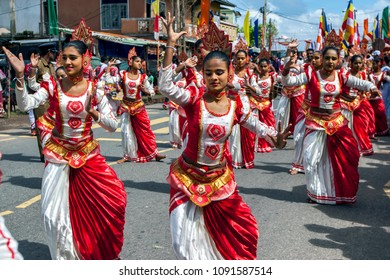 HIKKADUWA, SRI LANKA - SEPTEMBER 08, 2013 : Colourful female dancers perform along the coastal road during the Buddhist perahera (procession).