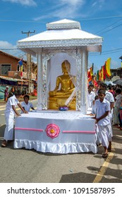 HIKKADUWA, SRI LANKA - SEPTEMBER 08, 2013 : A float carrying a golden statue of Lord Buddha is pushed along the coastal road at Hikkaduwa during a Buddhist perahera (procession).