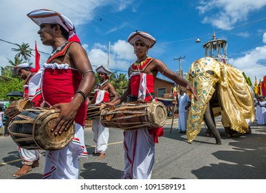 HIKKADUWA, SRI LANKA - SEPTEMBER 08, 2013 : Gatabera Players (Getaberakaruwo) perform ahead of a ceremonial elephant along the coastal road during the Buddhist perahera (procession).