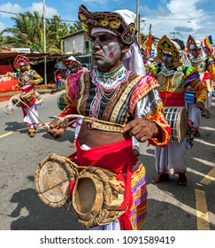 HIKKADUWA, SRI LANKA - SEPTEMBER 08, 2013 :  A Thammattam Player leads a group of musicians along the coastal road during the Buddhist perahera (procession).