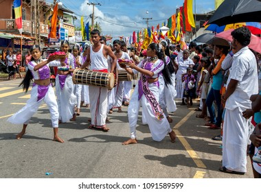 HIKKADUWA, SRI LANKA - SEPTEMBER 08, 2013 : Sri Lankan girls dance to the beat of Yak Beraya drums along the coastal road during the Buddhist perahera (procession).