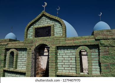 Hilal crescent moon and blue domes on Muslim green brick mausoleums at a cemetery near Shelek, Kazakhstan - September 8, 2016
