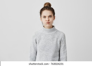 Hilarious caucasian girl with trendy hairstyle blowing her cheeks and frowning forehead. Persistant woman requiring attention grimacing being sassy. Emotions concept