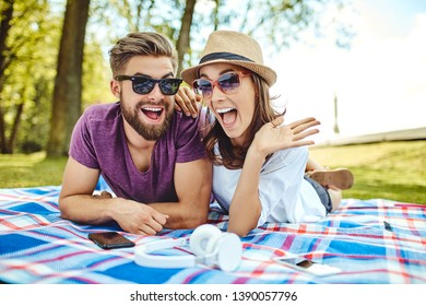 hilarious couple lying on a blanket in the park posing for photo