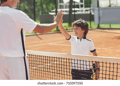 Hilarious laughing boy and man ready for tennis