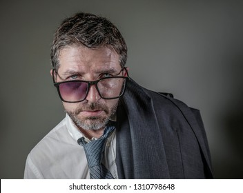 hilarious portrait of 40s weird and wasted businessman in suit and tie wearing ridiculous big broken nerdy glasses posing exhausted feeling a loser isolated on grey background as unsuccessful man