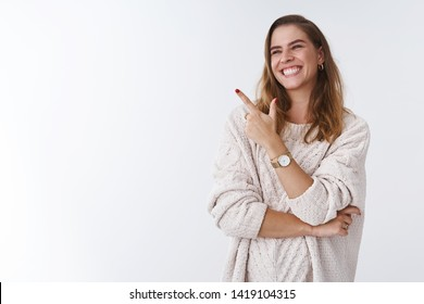Hilarious scene woman cannot stop laugh. Carefree attractive joyful charming girl turning sideways pointing left corner smiling amused having fun watching funny tv series, standing white background