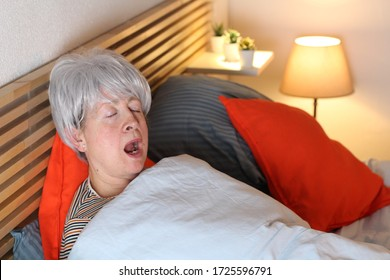 Hilarious senior woman snoring in bed