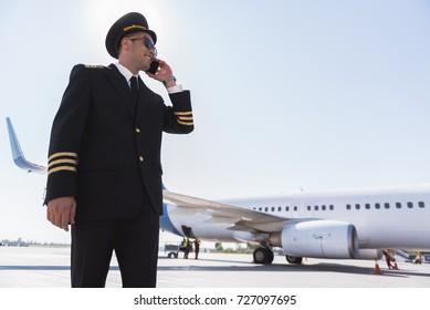 Hilarious smiling aviator using phone outside