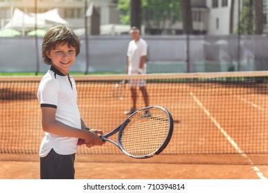 Hilarious smiling boy keeping racket