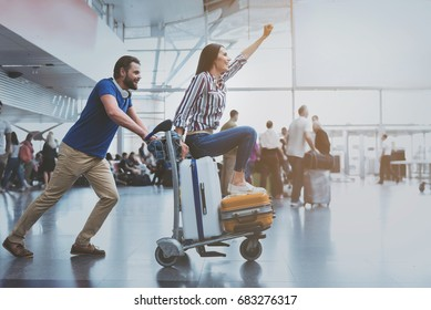 Hilarious smiling couple playing at terminal