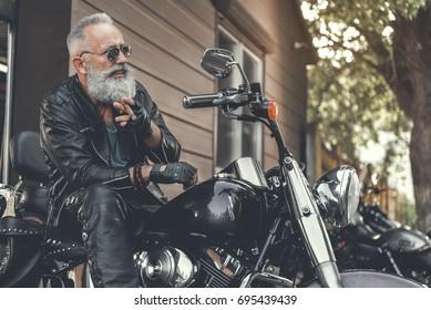 Hilarious smiling old man keeping smoke