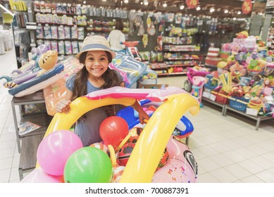 Hilarious smiling small lady among toys in supermarket