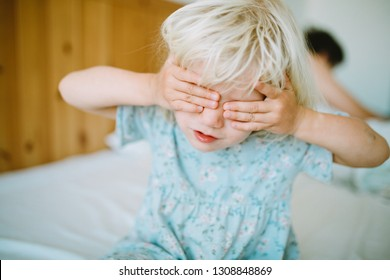 hild little girl cover her face with hands