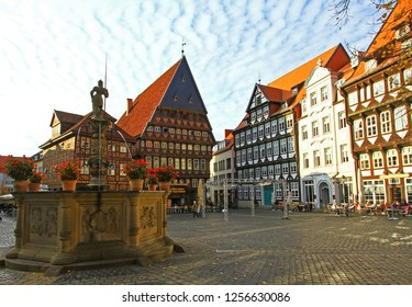 Hildesheim, Germany - November 1, 2016:  Ancient fountain with sculpture of knight (watchman) and sandstone reliefs at historic Market square in Old Town with fachwerk houses. Tourist destination.