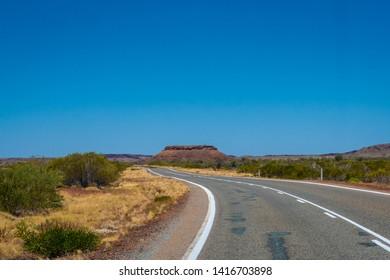 Hill behind empty road in Western Australia leading towards Karijini National Park