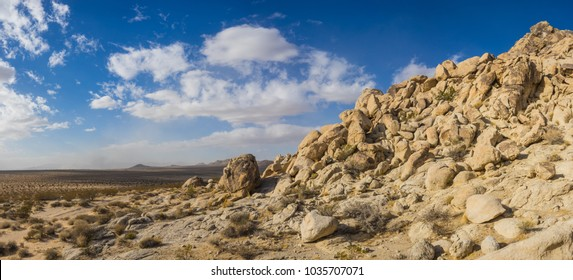 Hill composed of large sandstone boulders piled high in the sandy wilderness of a desert climate.