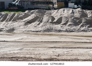 Hill of dirt at excavation worksite. Construction equipment iin blurred background.