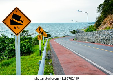 Hill or Downgrade Traffic Sign and other traffic sign beside road with seascape in Thailand.