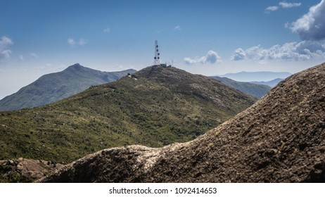 Hill with green creeping nature and tower with antennae at the top. In the background a chain of mountains and the scene framed by a rock.