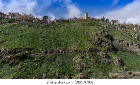 Hill lined with green grass with some historical constructions above and a detail of medieval wall on the top right at Toledo, Spain