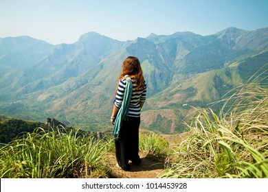 Hill station in Western Ghat mountains in Kerala, India. Young woman (back view) wearing scarf observing mountains from the hill, South India