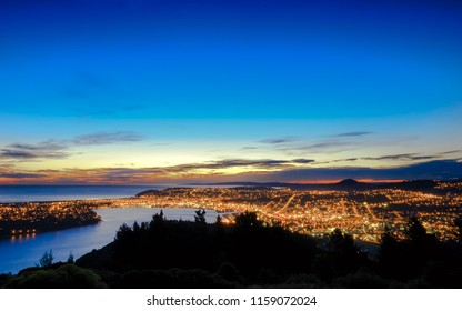 Hill top view of Dunedin City. From the top, one can enjoy beautiful city lights, sunset and colorful sky. Dunedin is a popular tourist destination in South Island of New Zealand.