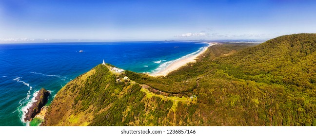 Hill tops of Smoky Cape with elevated while lighthouse facing vistas of Pacific ocean on NSW North coast in Australia. MId-air panorama over lush woods of national park.