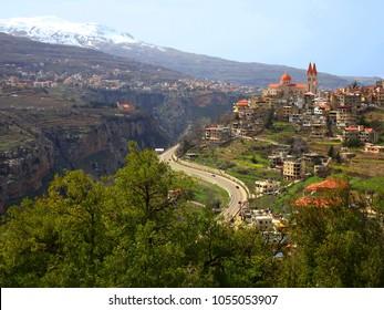 Hill town of Bsharri and Qadisha Valley (Kadisha Gorge / Wadi Kadisha / Ouadi Qadisha) Bcharreh, Liban-Nord, Lebanon. City on hill with Saint Saba Cathedral and valley with snow peak of Mount Lebanon.