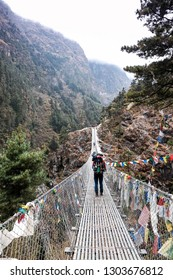 Hillary suspension bridge in Himalayas with prayer flags