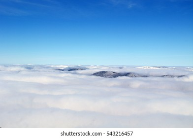 The hills are covered with forests peek out from the clouds
