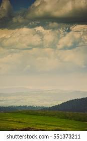 Hills covered with green grass under blue sky Summer landscape background