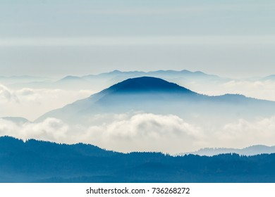 Hills and mountains over mist and clouds