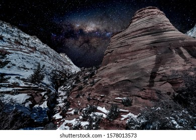 Hills and snow covered cliffs under the Milky Way sky in Zion National Park near Springdale, Utah, USA.