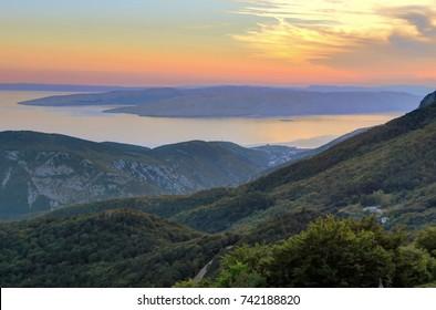 Hills voerlook purple, pink, and orange sunset behind the purple blue water of the Adriatic sea near Senj, Croatia