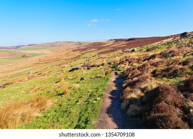 A hillside footpath travels across the Derbyshire Peak District on a bright spring morning