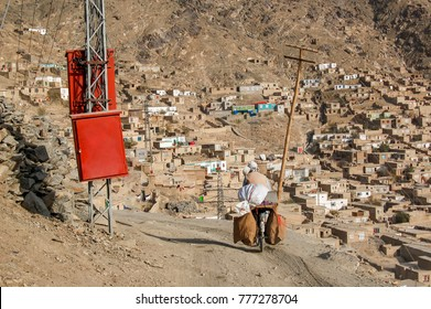 The hillsides of Kabul Afghanistan with its informal settlements with two males transporting goods on a bicycle near an electricity pole