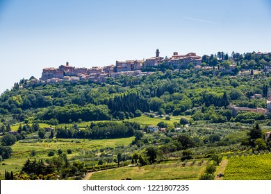 A hilltop medieval town in Tuscany above mountains and trees on a sunny day