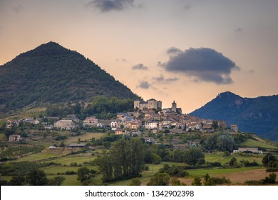 Hilltop Village in Cevennes valley landscape near Le Rozier with mountains and hills under colorful sky