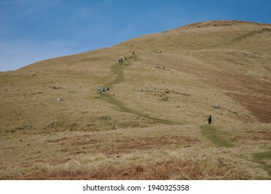 Hillwalkers climbing a hill in the Ochil Hills in Scotland during a blue spring day