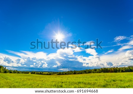 Hilly fields among forests in the background of the sun with cumulus clouds. Wide angle view