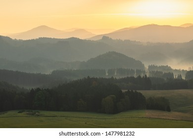 Hilly landscape during warm and bright sunrise. Very peaceful and pleasing scene. Forests and hills without any industry or buildings.